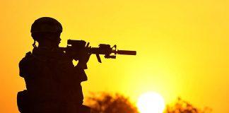 A MARSOC Marine patrols through the village in Farah province
