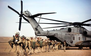 U.S. Marines and Afghan border police off-load from a CH-53D Sea Stallion helicopter